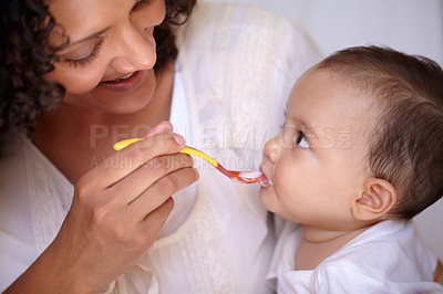 Buy stock photo A cute baby girl being fed by her mother