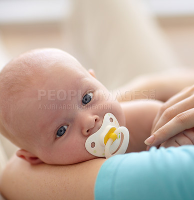 Buy stock photo A cute baby boy sucking on a pacifier looking up from his mother's arms