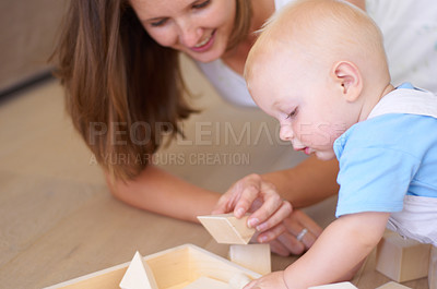 Buy stock photo A young mother playing with building blocks along with her baby son