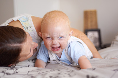 Buy stock photo A young mother making her baby son laugh while lying on her bed