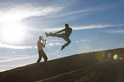 Buy stock photo Two male kickboxers practising on top of a mountain