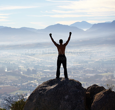 Buy stock photo Rearview of a man with his arms raised while standing on a mountain top