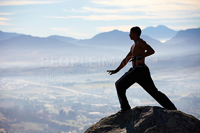 Buy stock photo A male kickboxer high up on a mountain top to practice