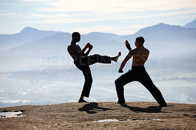 Buy stock photo Two male kickboxers competing with one another on a mountain top
