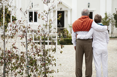 Buy stock photo Rear view of a senior couple embracing each other in the courtyard of their hotel