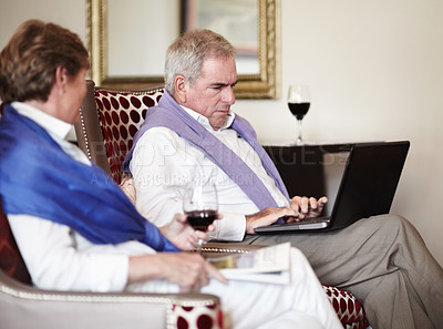 Buy stock photo A senior man on his laptop while enjoying drinks with his wife