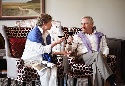 Buy stock photo A senior couple enjoying a glass of red wine together while on vacation