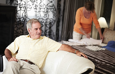 Buy stock photo A senior man talking to his wife as she unpacks their clothing while on vacation