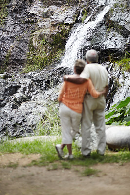 Buy stock photo Rear view of a senior couple embracing and admiring a picturesque waterfall