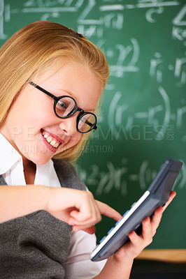 Buy stock photo A cute blonde girl using a calculator in maths class