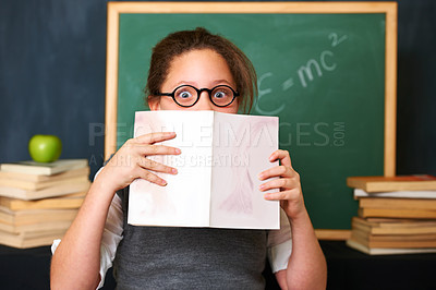 Buy stock photo Portrait of a cute brunette girl holding a book in front of her face