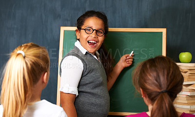 Buy stock photo Portrait of a cute girl showing her two classmates something on the chalkboard in class