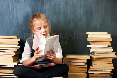 Buy stock photo A cute blonde girl reading in class surrounded by books