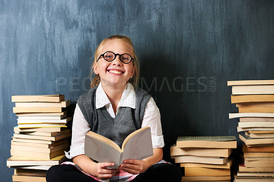 Buy stock photo A happy blonde girl reading in class surrounded by books