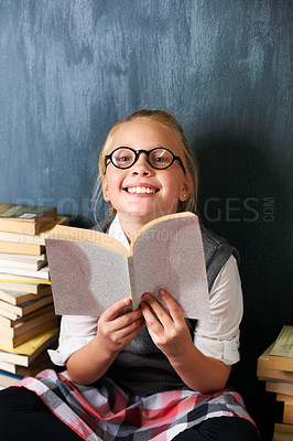 Buy stock photo A happy blonde girl studying in class surrounded by books