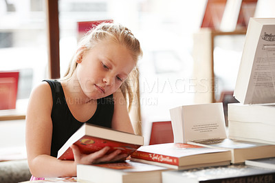 Buy stock photo A cute blonde girl looking at the cover of a book in the library