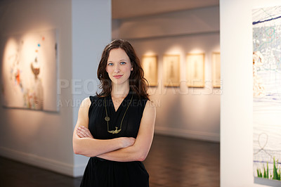 Buy stock photo A portrait of a young woman standing in front of numerous paintings hanging on the walls of a gallery