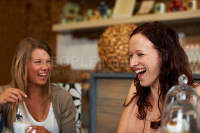 Buy stock photo Two female friends sharing a laugh while sitting in a cafe
