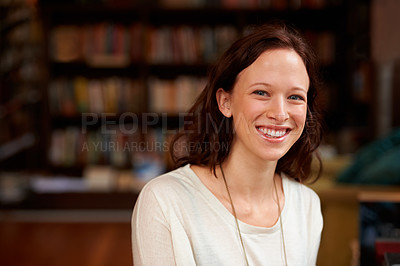 Buy stock photo Portrait of a smiling young woman against a background of bookshelves