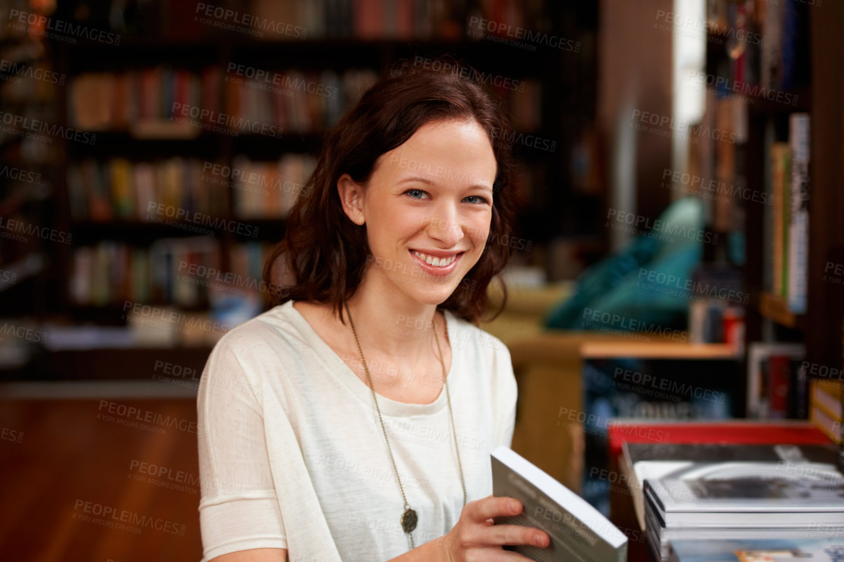 Buy stock photo Portrait of a young woman smiling happily while browsing in a bookstore