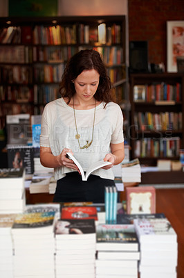 Buy stock photo A young woman leafing through the pages of a book in a bookshop