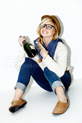 Buy stock photo Portrait of a gorgeous young blonde woman sitting and pointling  at a bottle of champagne