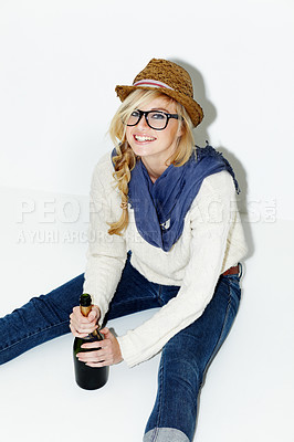 Buy stock photo Portrait of a gorgeous young woman sitting on the floor while holding a bottle of champagne