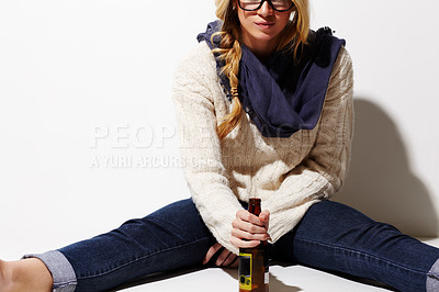 Buy stock photo Cropped image of a young woman holding a beer in front of her while sitting on the floor