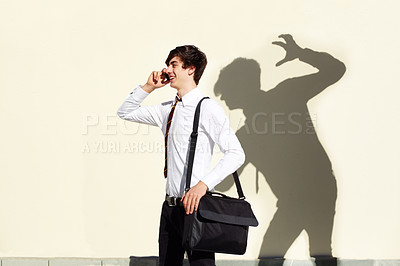 Buy stock photo Shot of a young man being stalked by a ominous shadow of himself