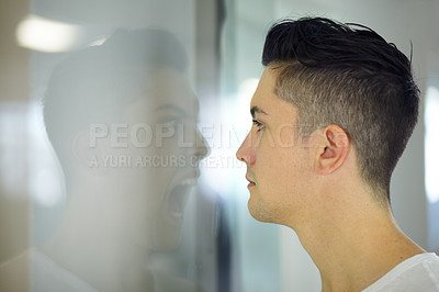 Buy stock photo Young man looking at a screaming reflection of himself