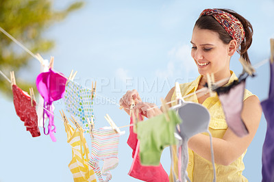 Buy stock photo Attractive young woman hanging up her washing on a line outside