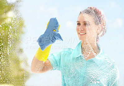 Buy stock photo Young woman washing her windows with a smile