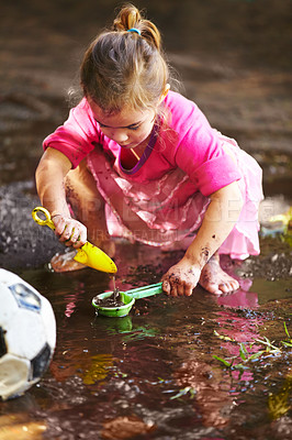 Buy stock photo Shot of a little girl playing outside in the mud