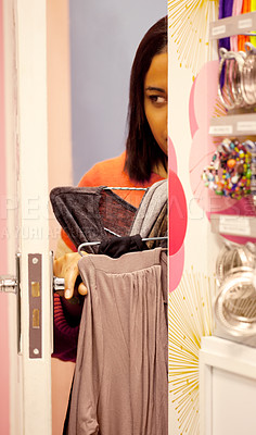 Buy stock photo Young woman trying to sneak out of a store with some garments