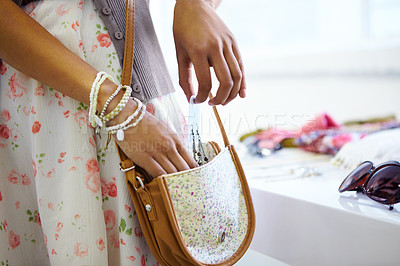 Buy stock photo Cropped shot of a young woman slipping stolen goods into her handbag