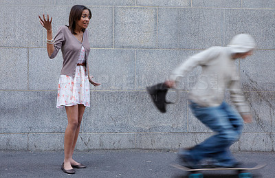 Buy stock photo Young woman having her bag snatched by a criminal on a skateboard