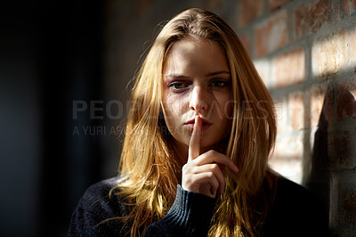 Buy stock photo Abused young woman making a silence gesture while looking at the camera