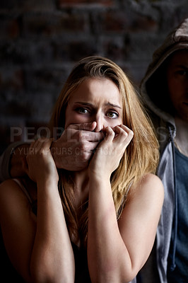 Buy stock photo Abused young woman being silenced by her abuser