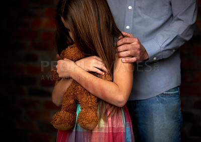 Buy stock photo Abused little girl with her abuser gripping her shoulder