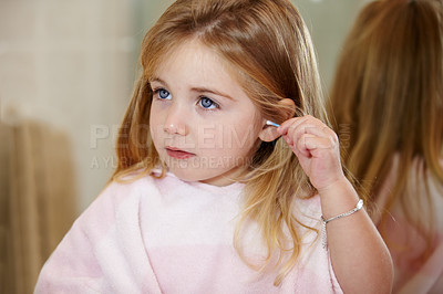 Buy stock photo Cute little girl cleaning her ears with an earbud