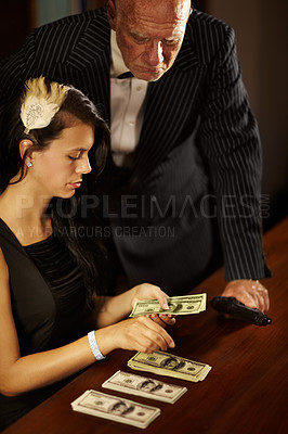 Buy stock photo Young woman counting money as a mob boss watches over her