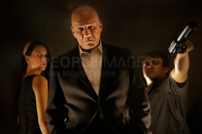 Buy stock photo Mob boss looking serious with his team standing behind him
