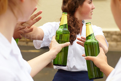 Buy stock photo Young female student turning down alcohol in response to peer pressure