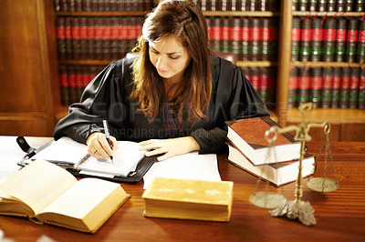 Buy stock photo Shot of a young legal professional sitting at her desk in a study