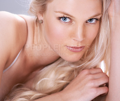 Buy stock photo Portrait of a stunning young blonde woman lying down with her hand in her hair
