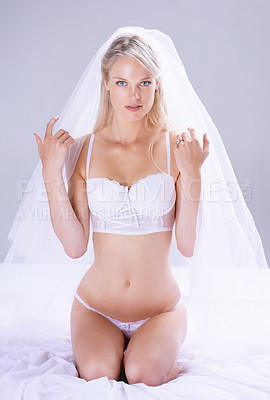 Buy stock photo Portrait of a beautiful young bride sitting on her bed in lingerie