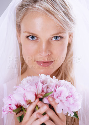 Buy stock photo Closeup portrait of a beautiful young bride holding up her bouquet