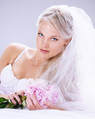 Buy stock photo Portrait of a beautiful young bride lying on her bed with a bouquet