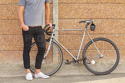 Buy stock photo A cropped shot of a young man standing next to a bicycle
