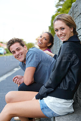 Buy stock photo Portrait of three young friends sitting on a roadside bench